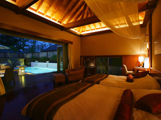 鴨川館別邸 ラ・松廬 花のライトアップされたプールを臨むベッドルーム