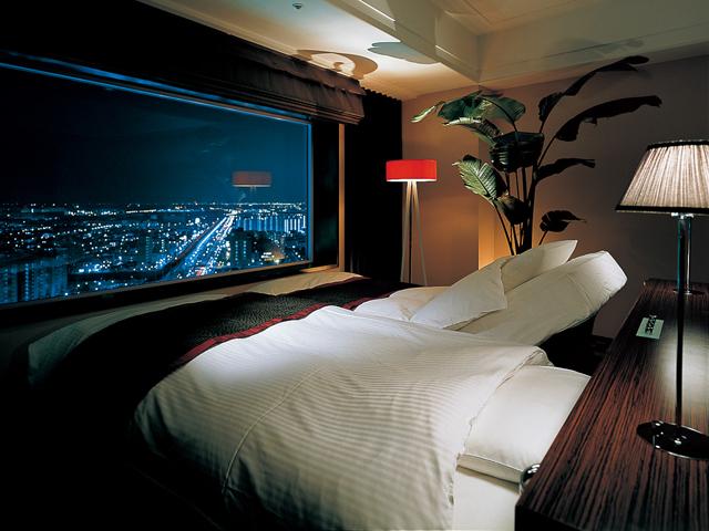 窓に向かってレイアウトされたベッドから夜景が楽しめる「ジ・アッパー12」