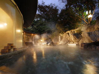 樹木の緑と巨岩に囲まれ、広がる空を天井とした野天のお風呂「龍神の湯」