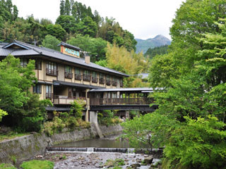 やまびこ旅館 茅葺きの門に迎えられ川を眺めながら橋を渡る静かな宿。巨石を配した大きな露天風呂、仙人の湯が有名。
