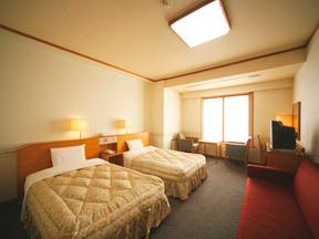 花巻温泉 ホテル千秋閣 壁に水彩画がかかるシンプルな洋間。赤いソファーがアクセント